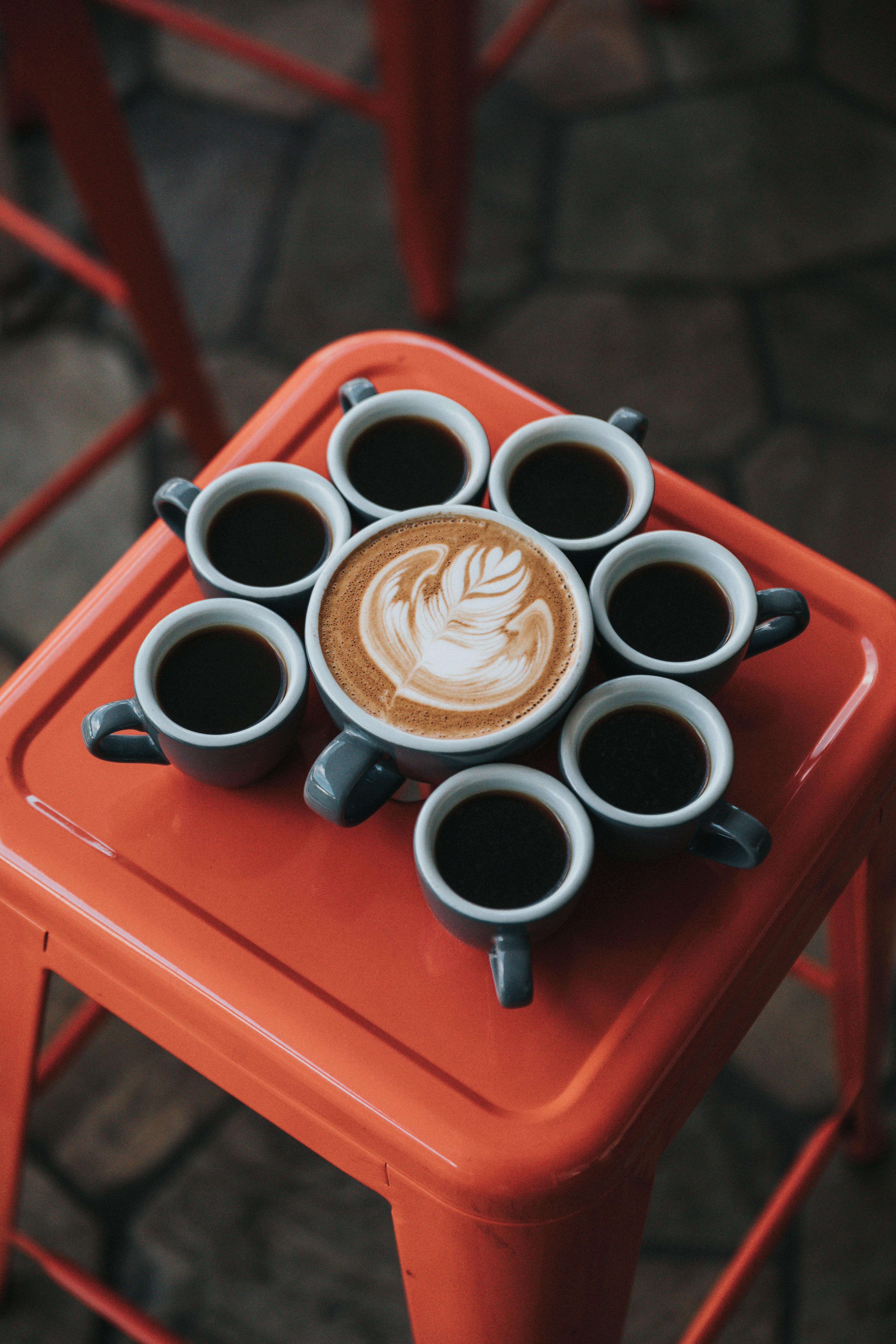 gray ceramic coffee mug set on top of red stool