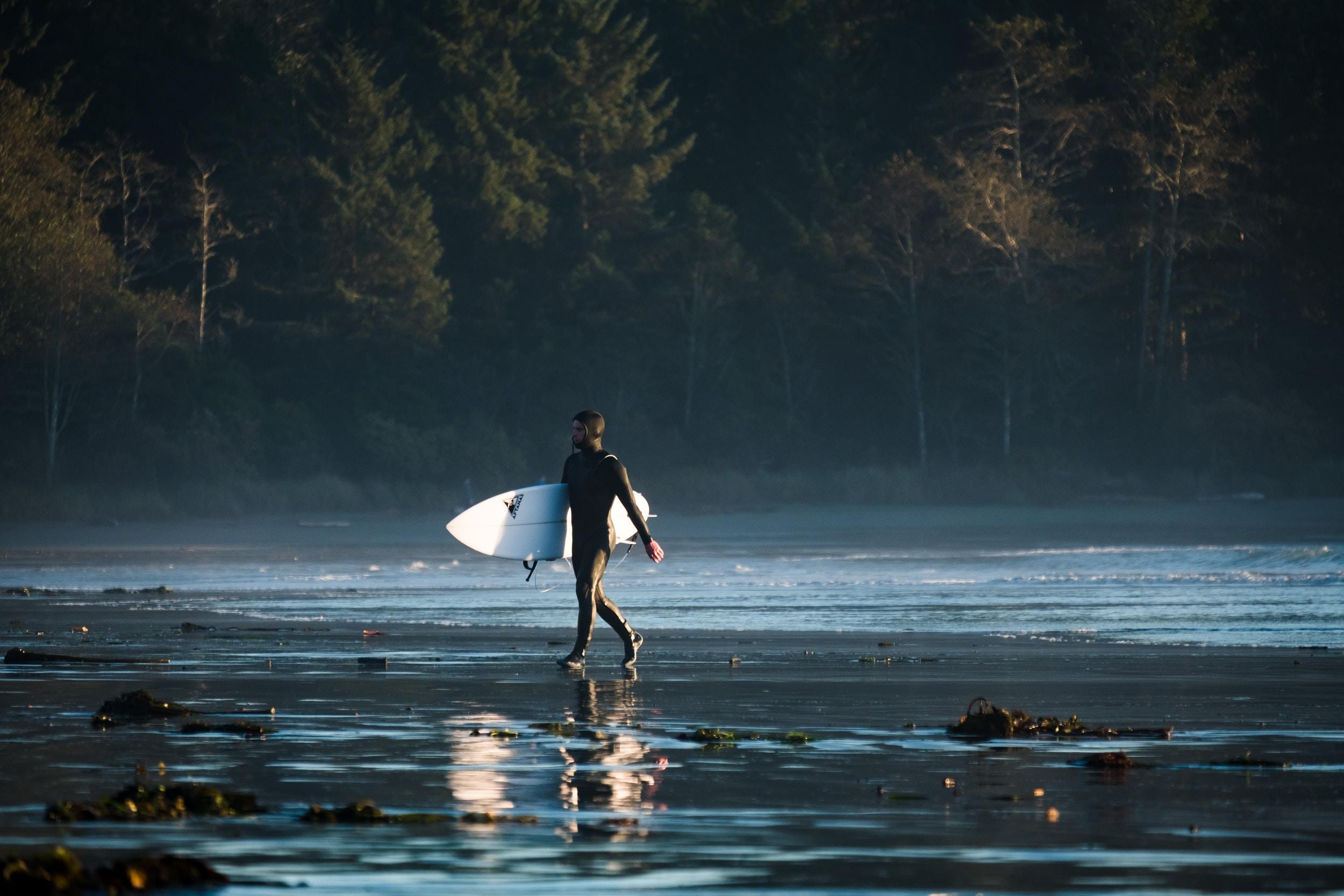 man carrying his white surfboard walking on seashore