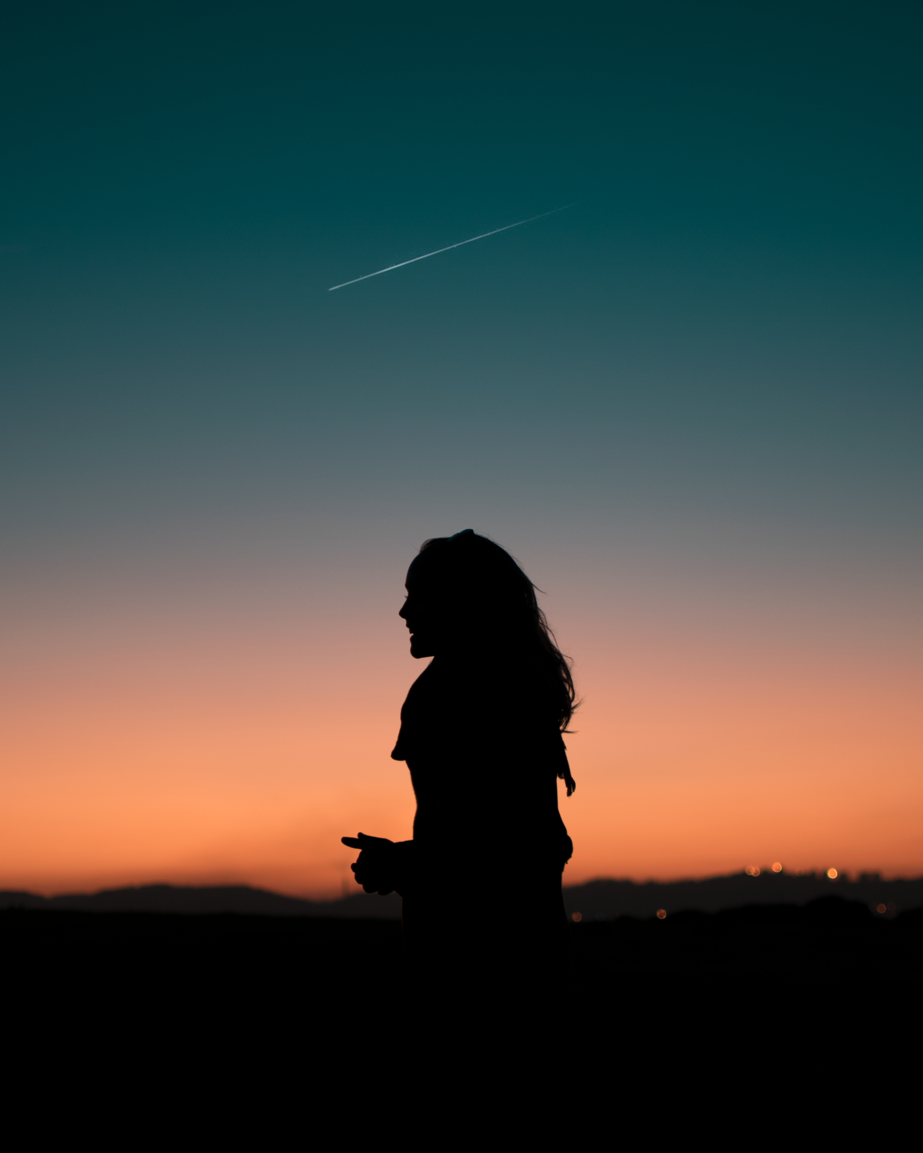 silhouette of woman standing under blue sky during golden hour