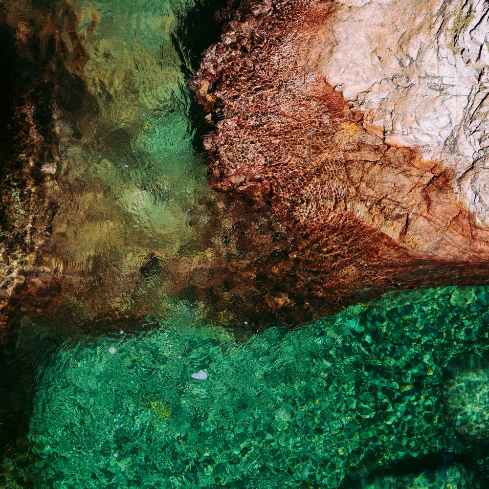 aerial photography of body of water and rock