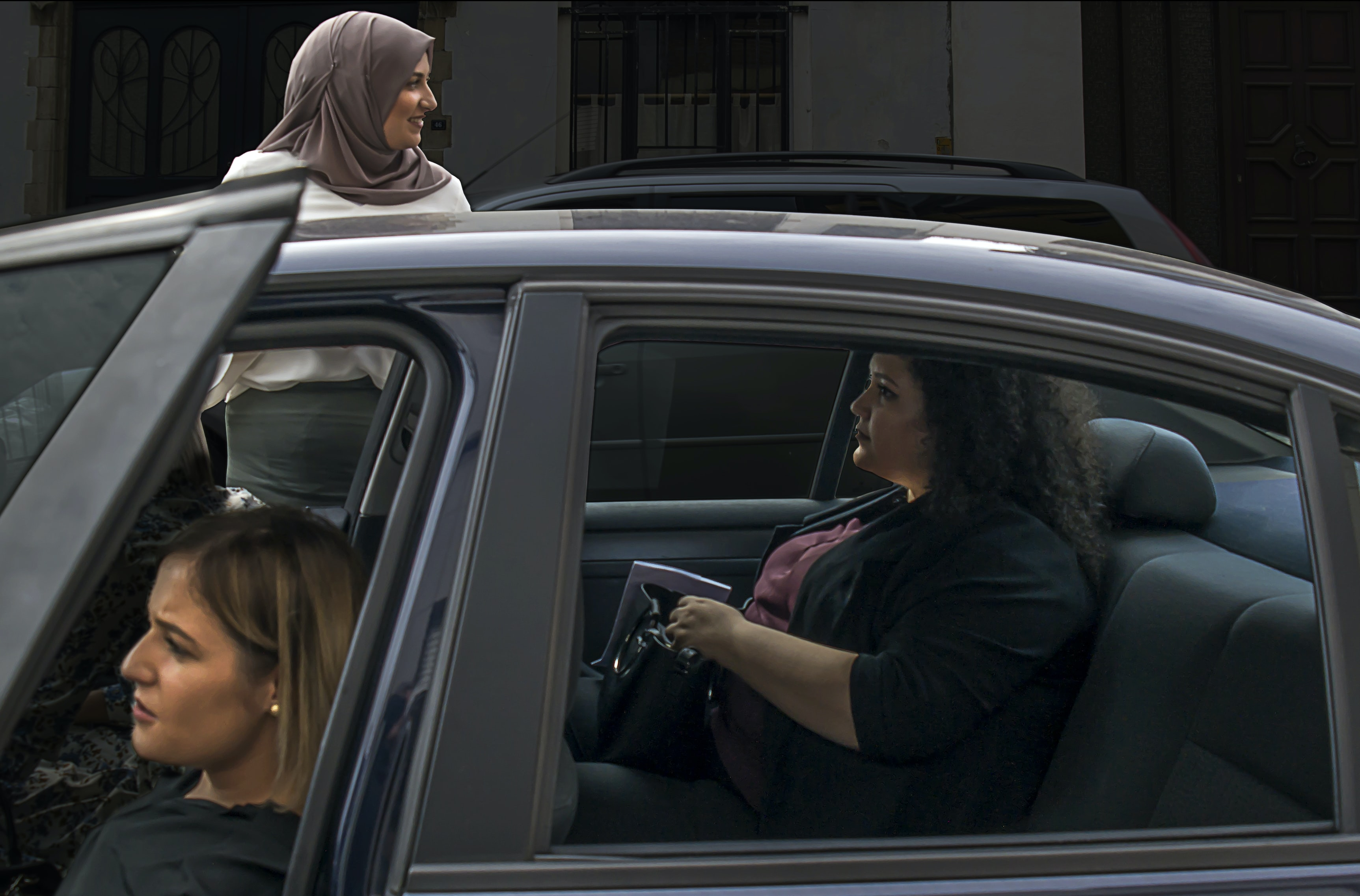 two woman inside vehicle beside woman on the outside wearing brown hijab headscarf during daytime