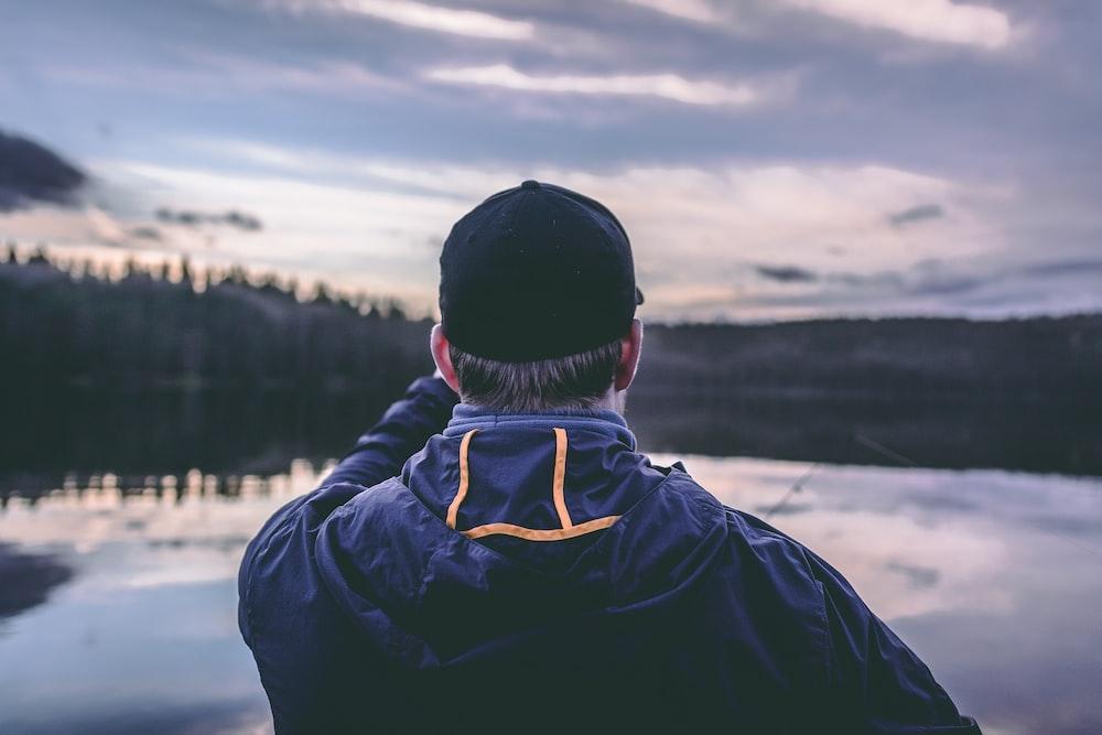 man wearing hoodie facing body of water
