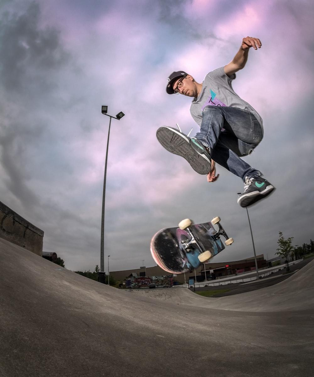 man in gray t-shirt and black pants playing skateboard