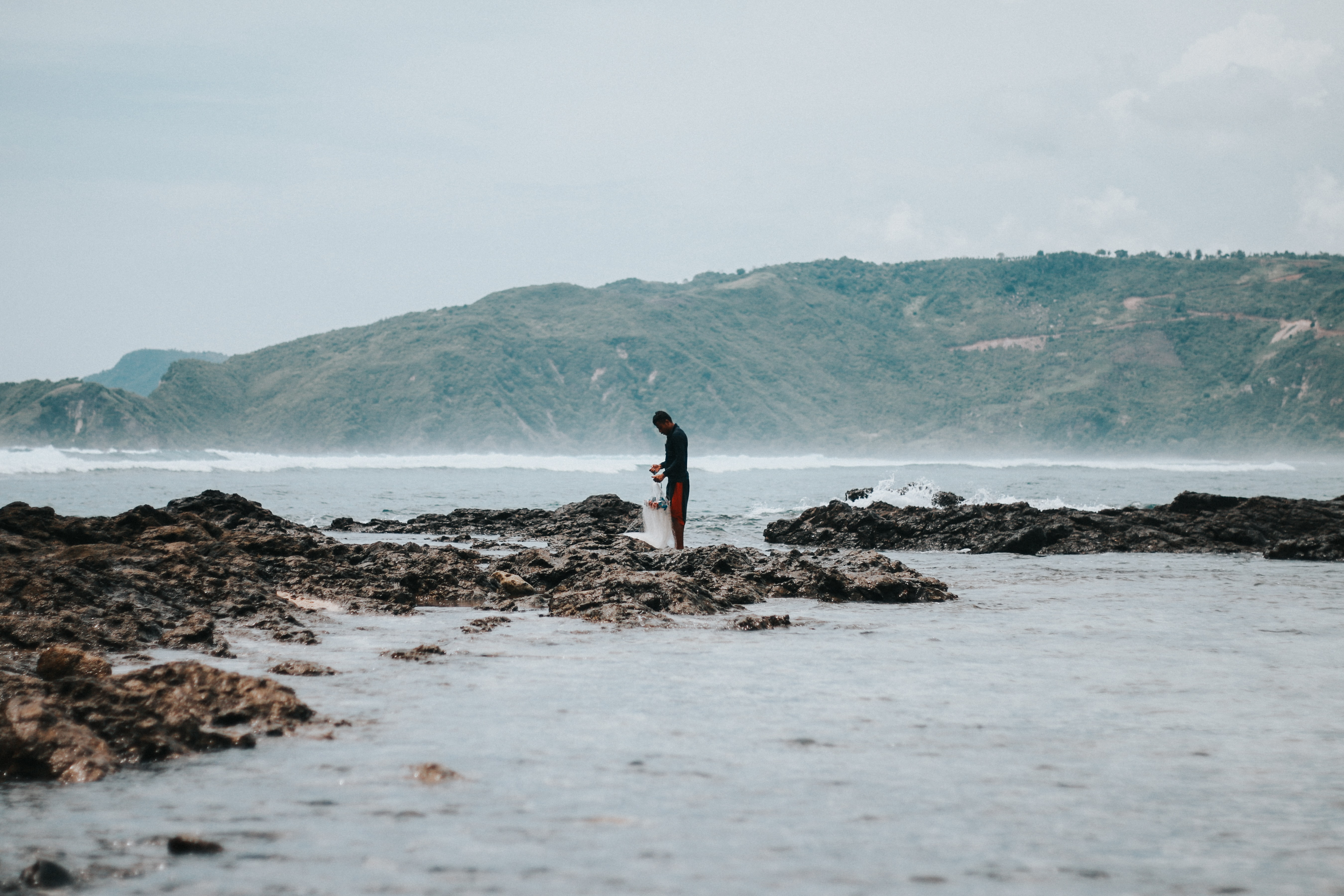man standing on rocky seashore during daytime
