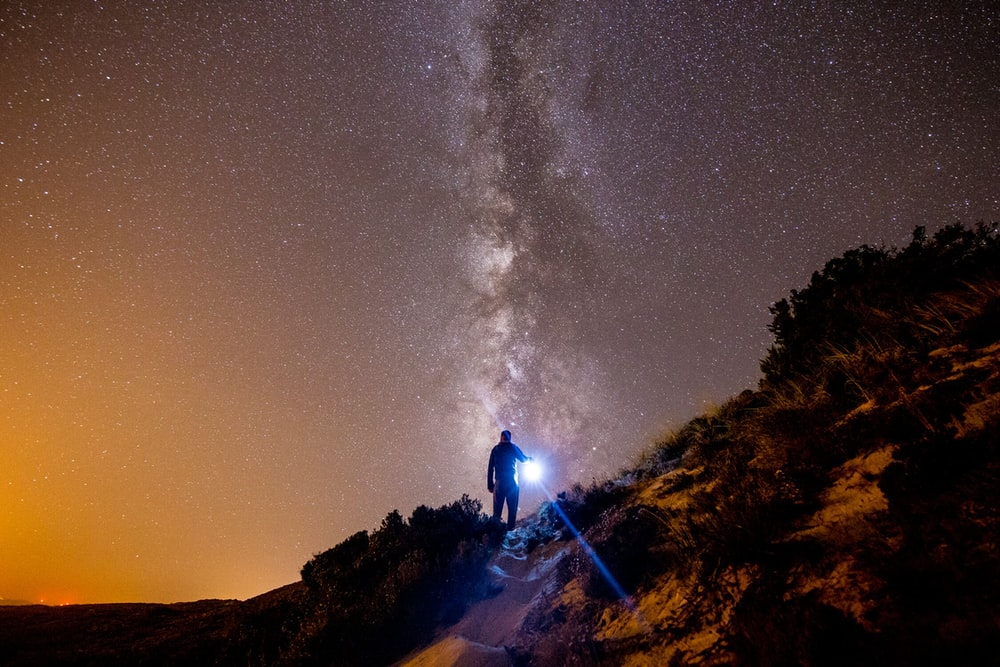 person on brown cliff under galaxy