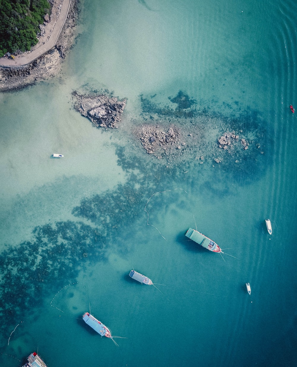aerial photo of boats anchored on shallow waters near beach during daytime
