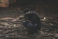 man sitting on black wood planks
