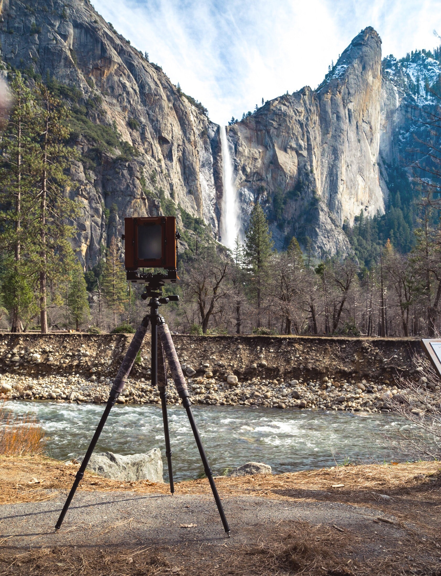brown camera with tripod near on body of water