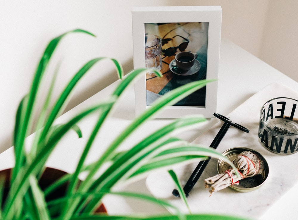 white and black photo frame near clear glass tray