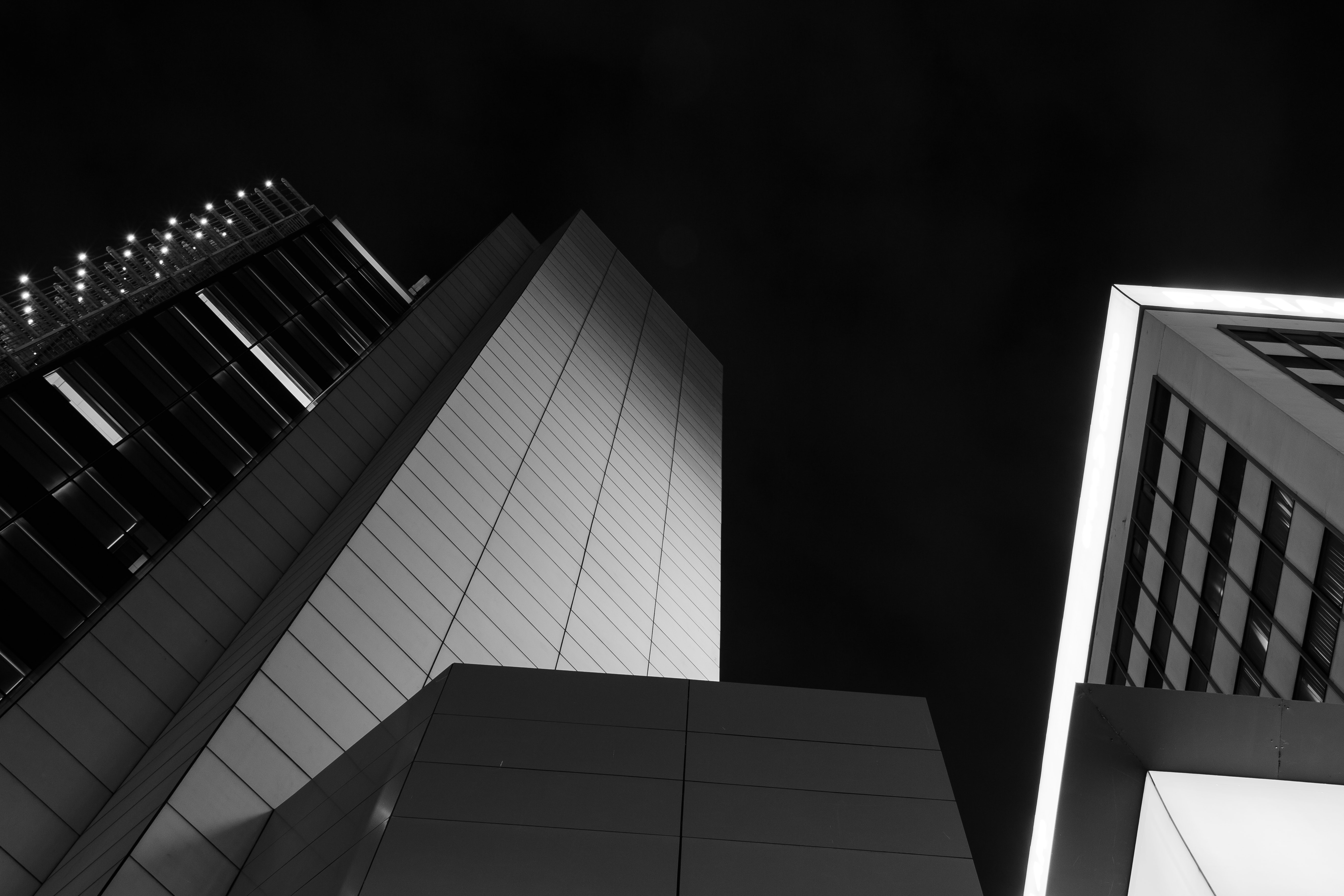 low angle photography of high-rise curtained wall building grayscale photo