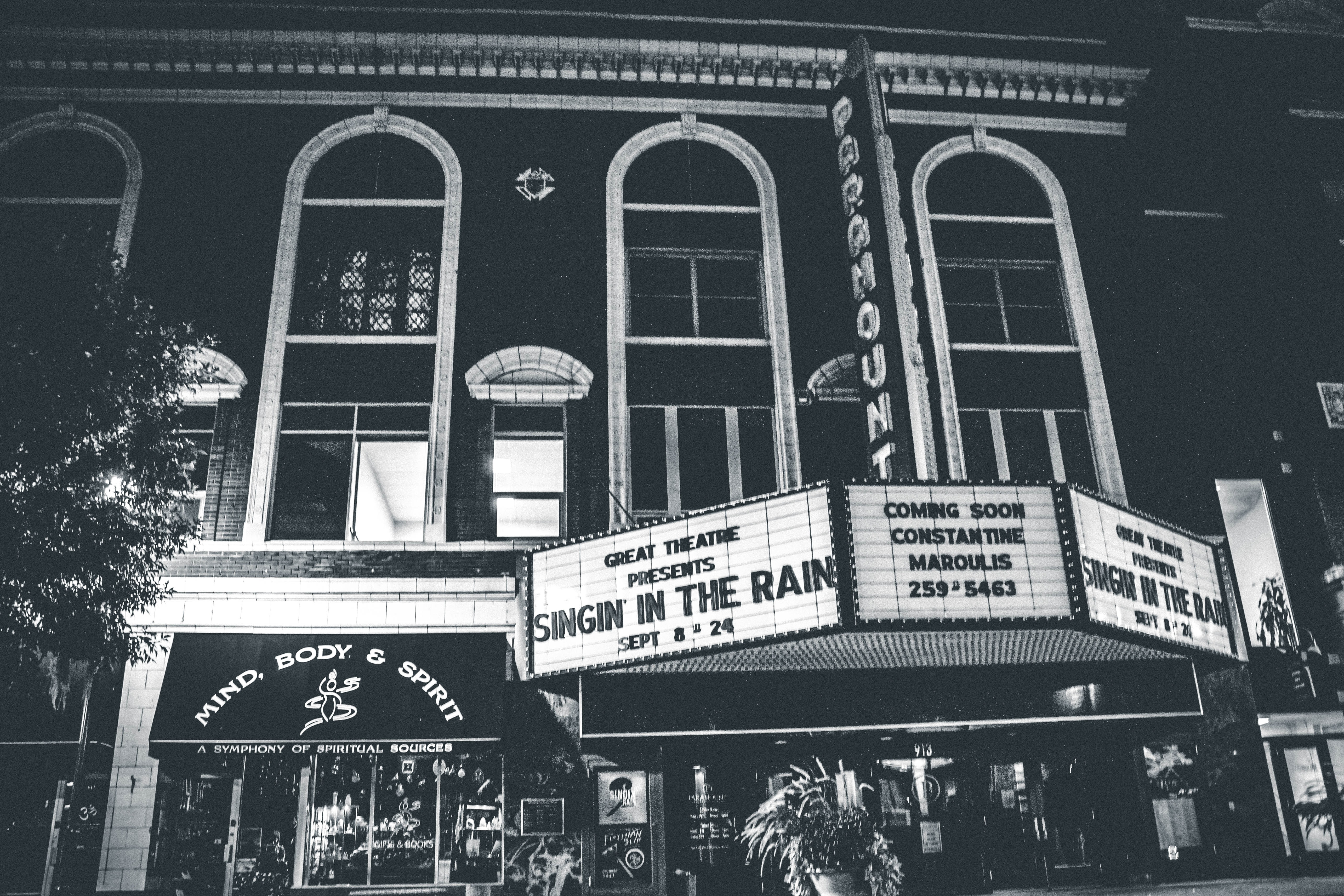 grayscale photo of theater hall with Singin in the Rain movie