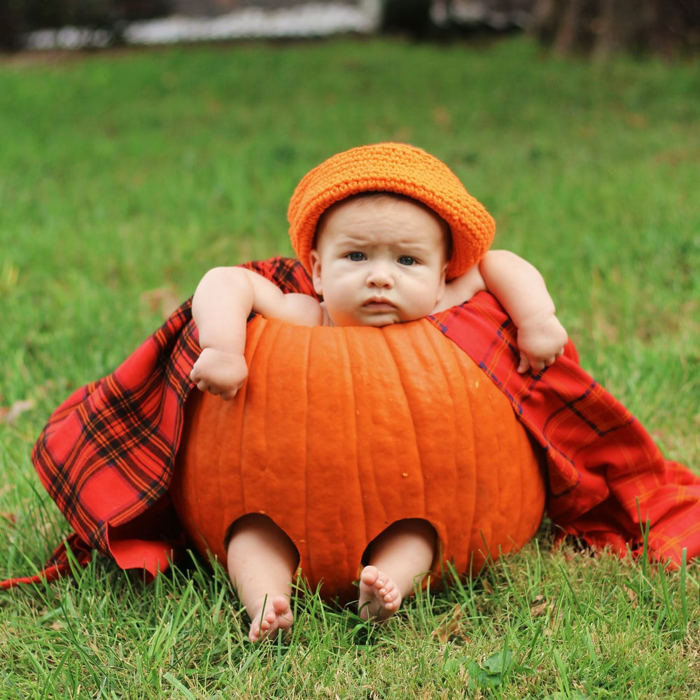 baby in red pumpkin