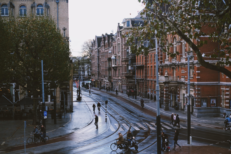 people walking on road near brown buildings during daytime