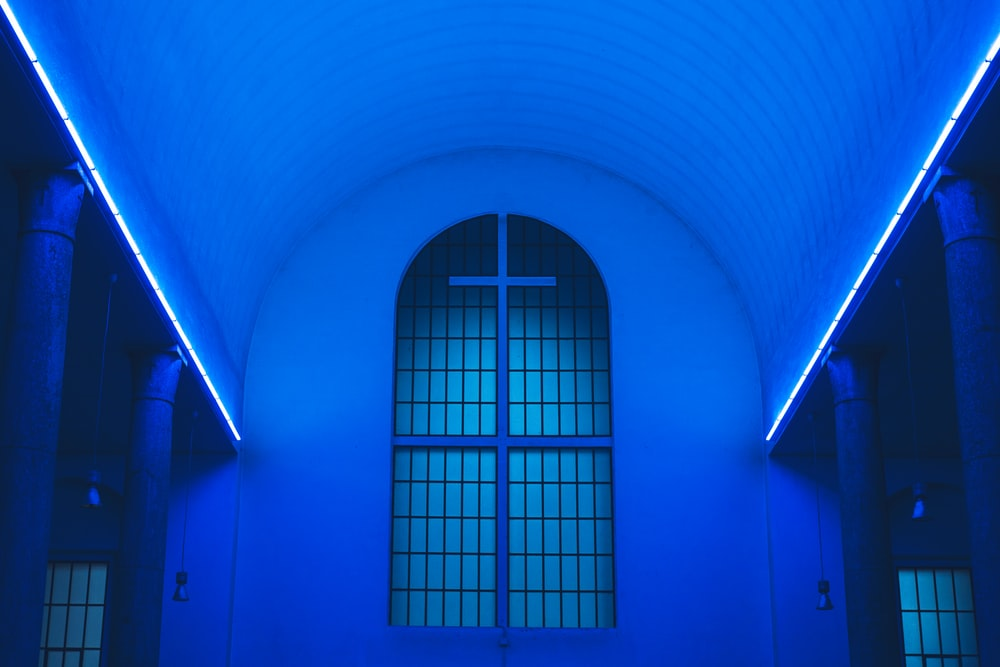 blue lighted ceiling fronting the white cross