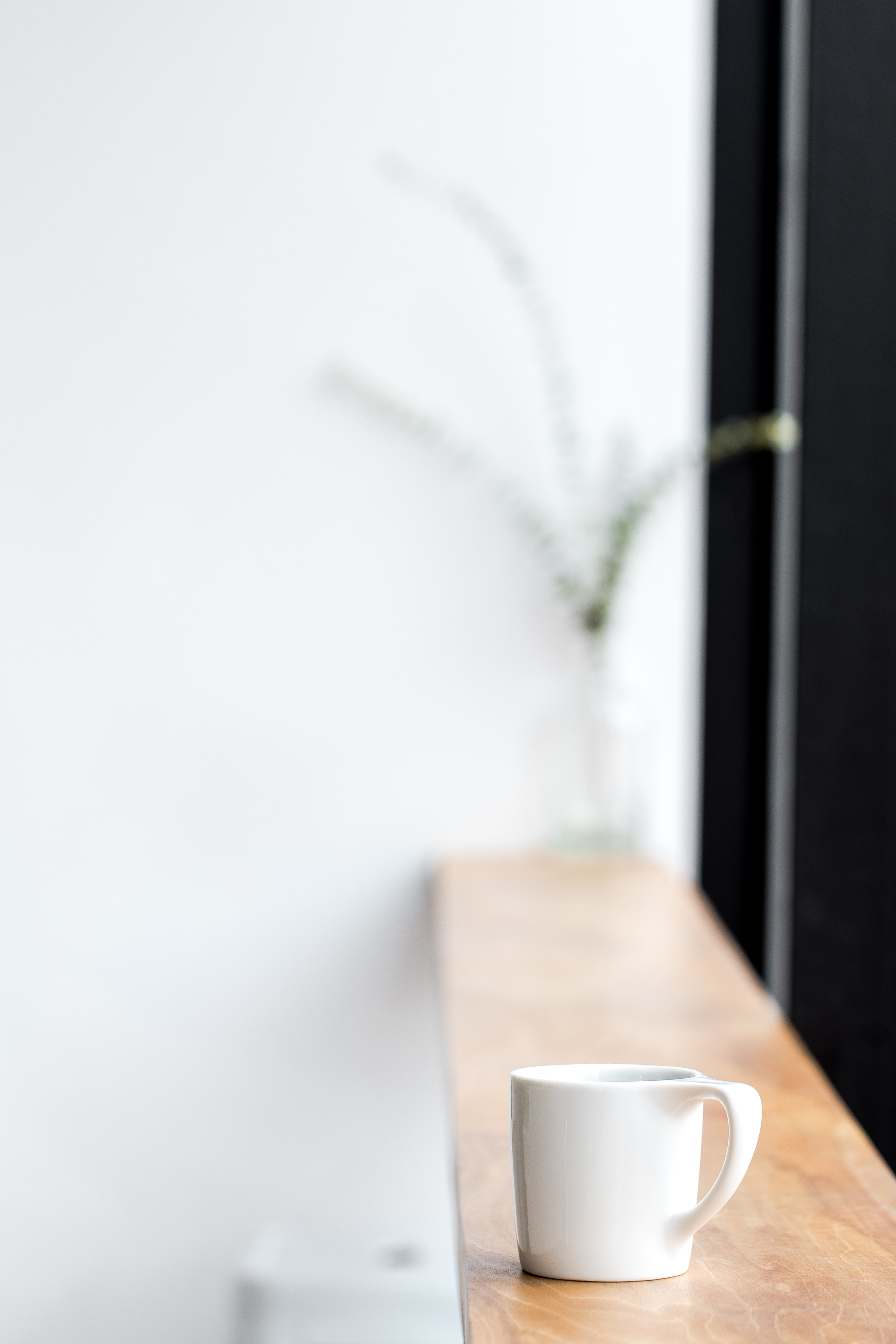 white ceramic mug on brown wooden board