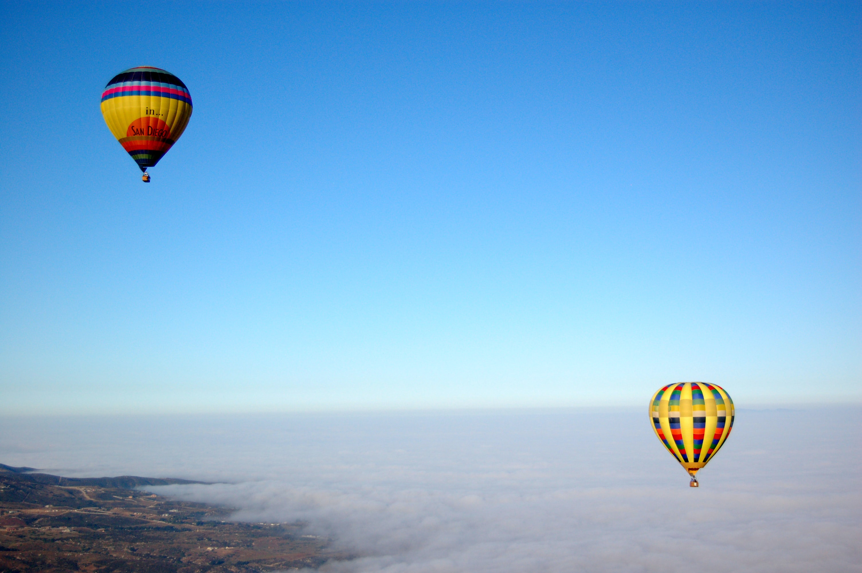 two hot air balloons flying over sky