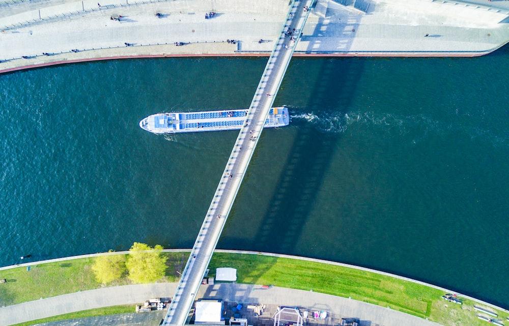 aerial photography of white boat passing under white bridge