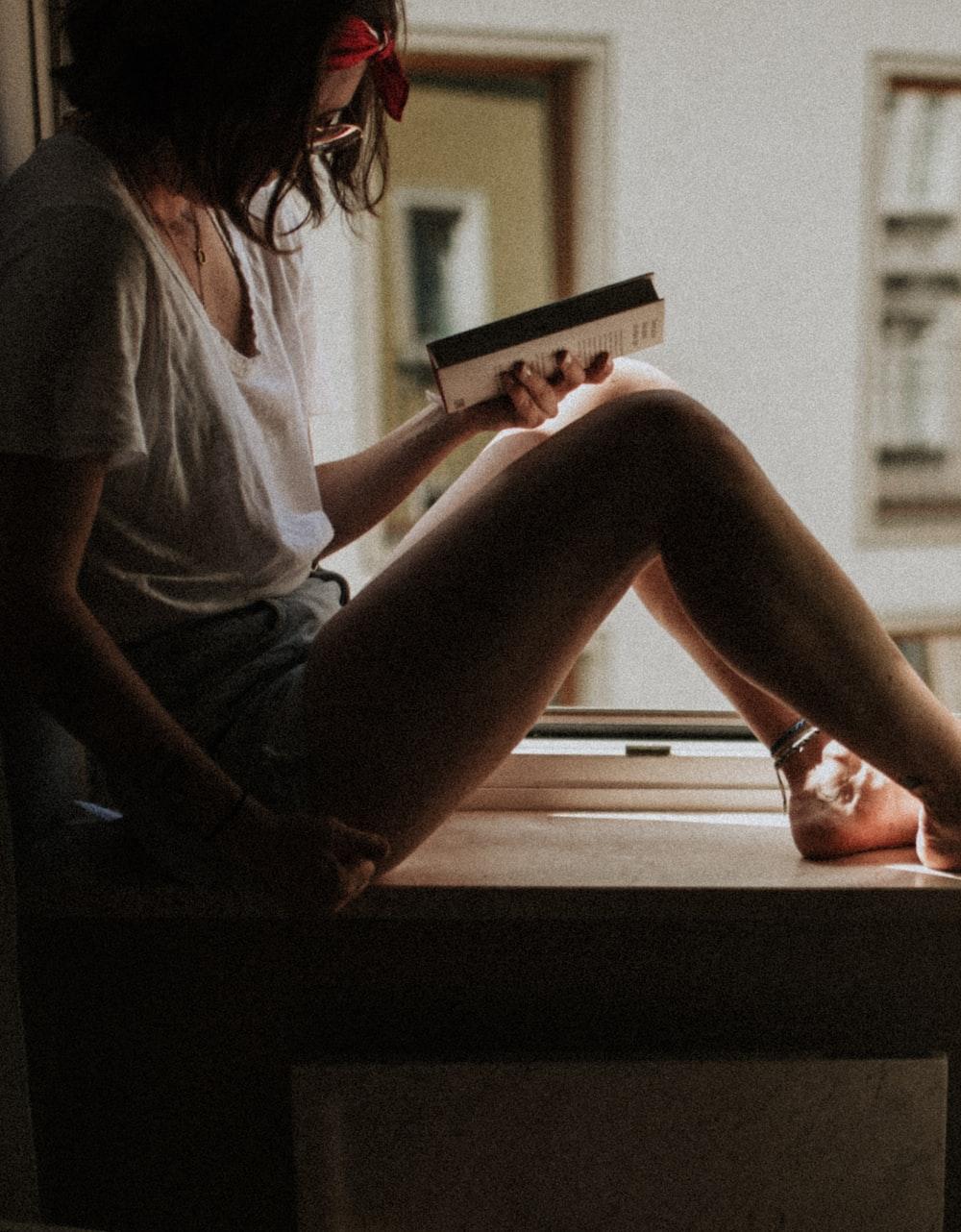 woman sitting on window holding book