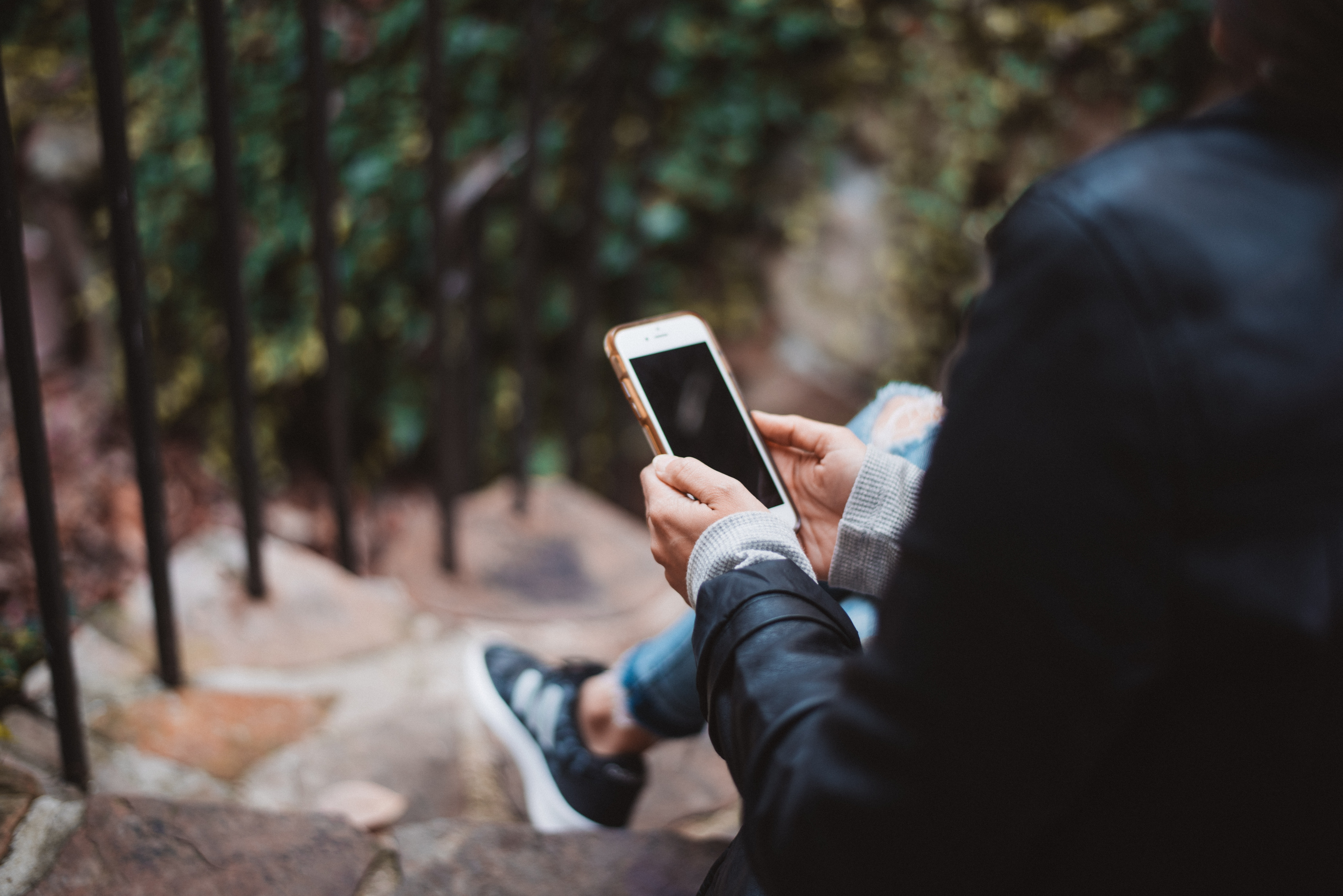 person holding white smartphone sitting on stair