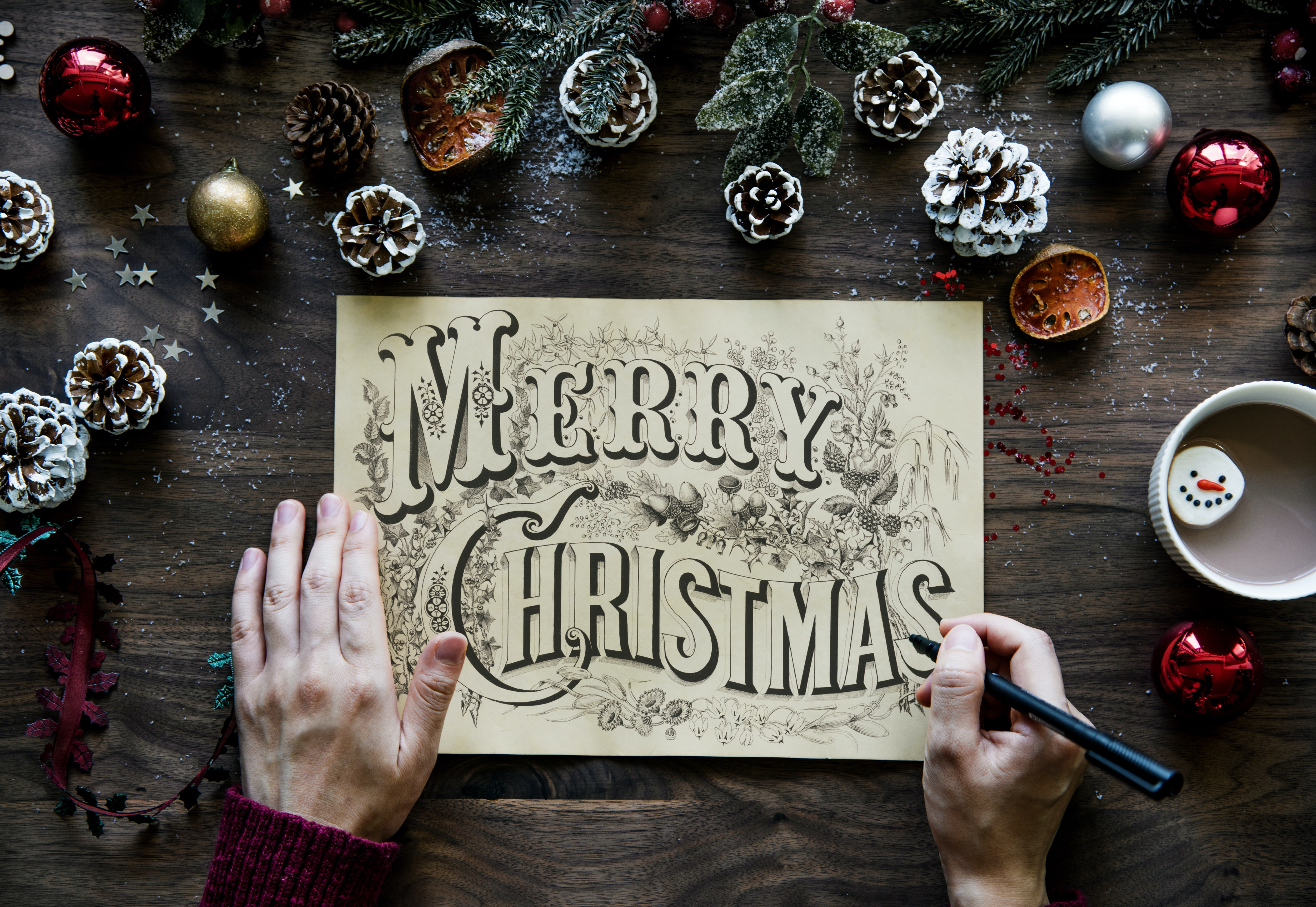 person writing Merry Christmas on paper in between Christmas decors