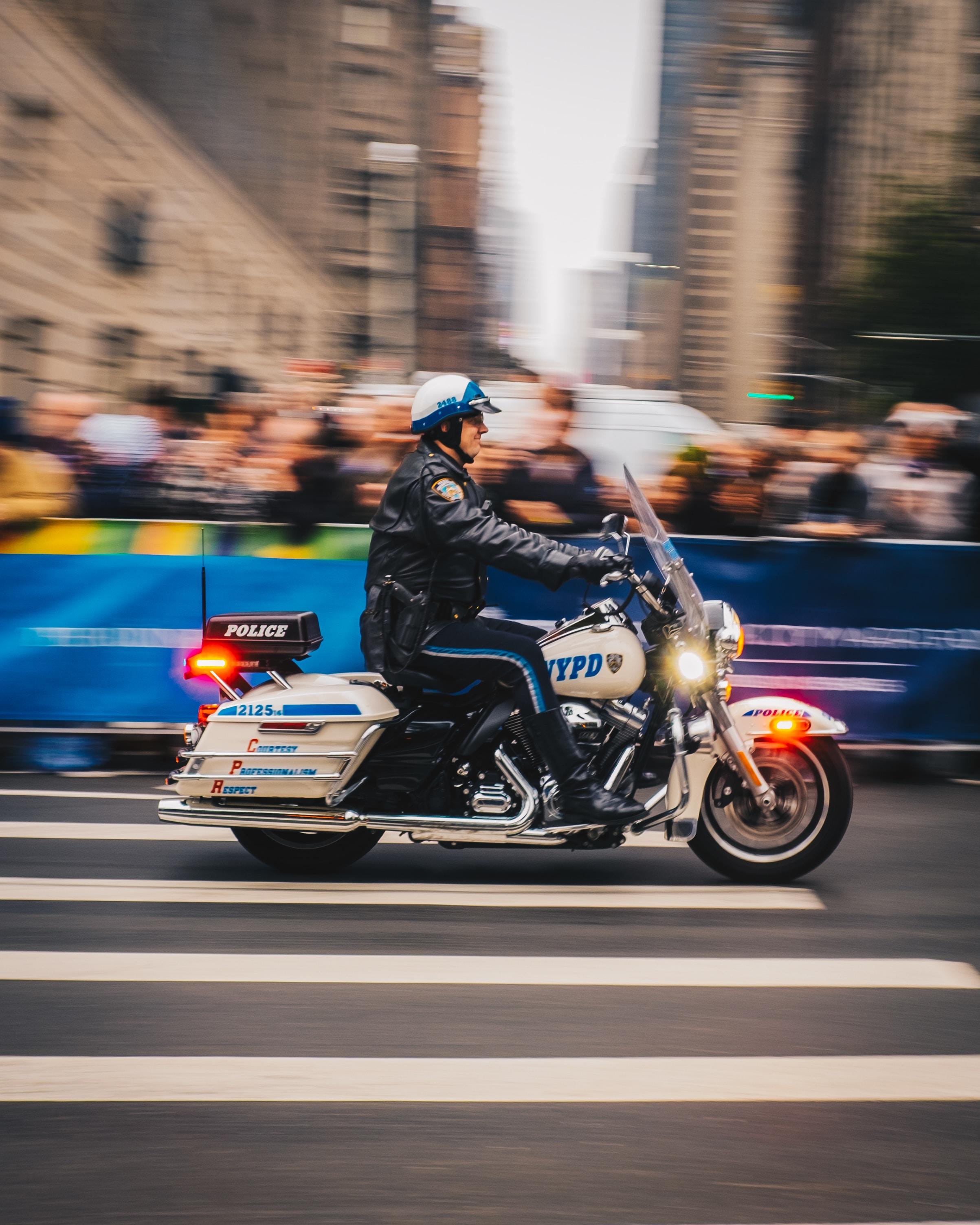 policeman riding on white motorcycle