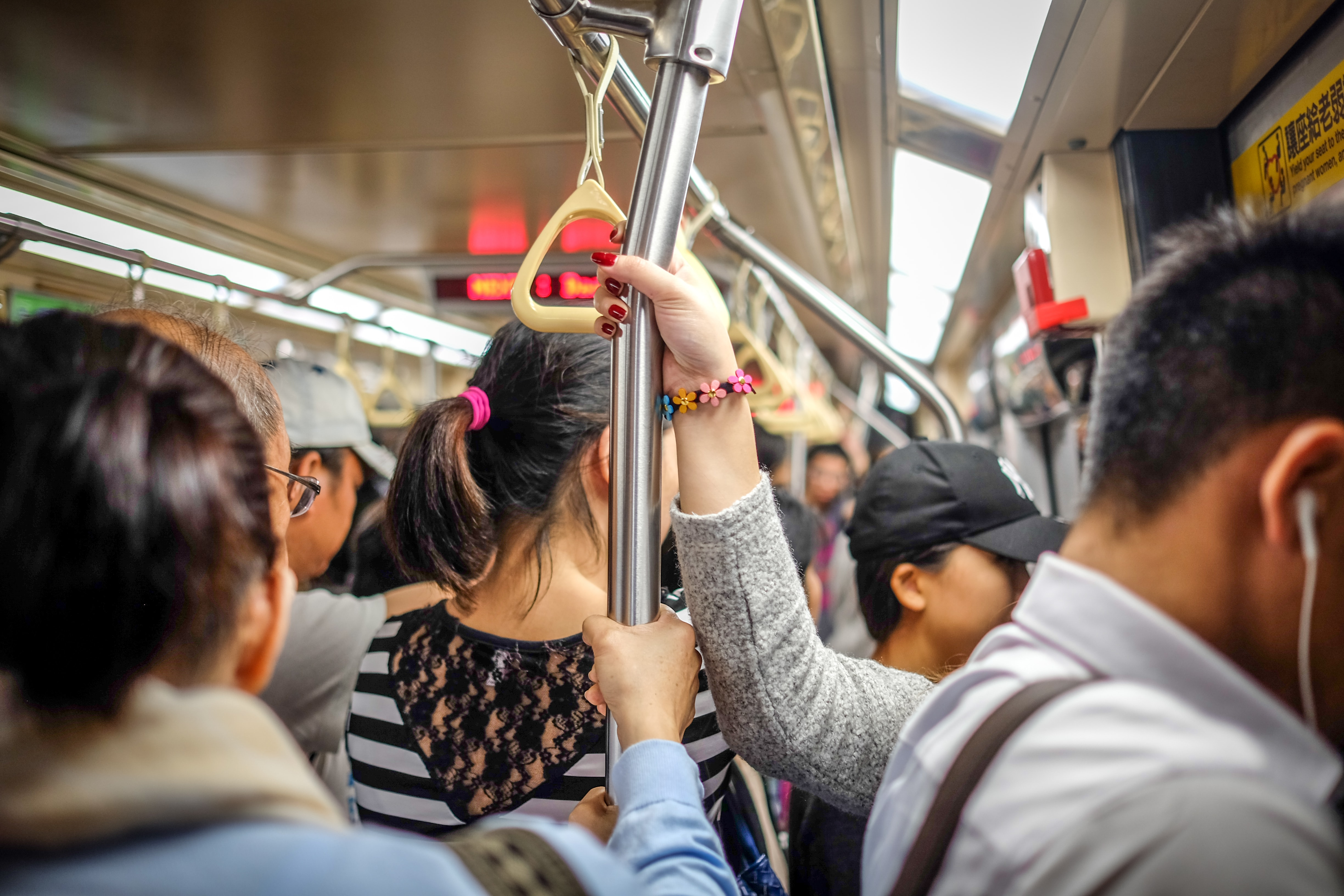 people holding metal pole while standing inside train