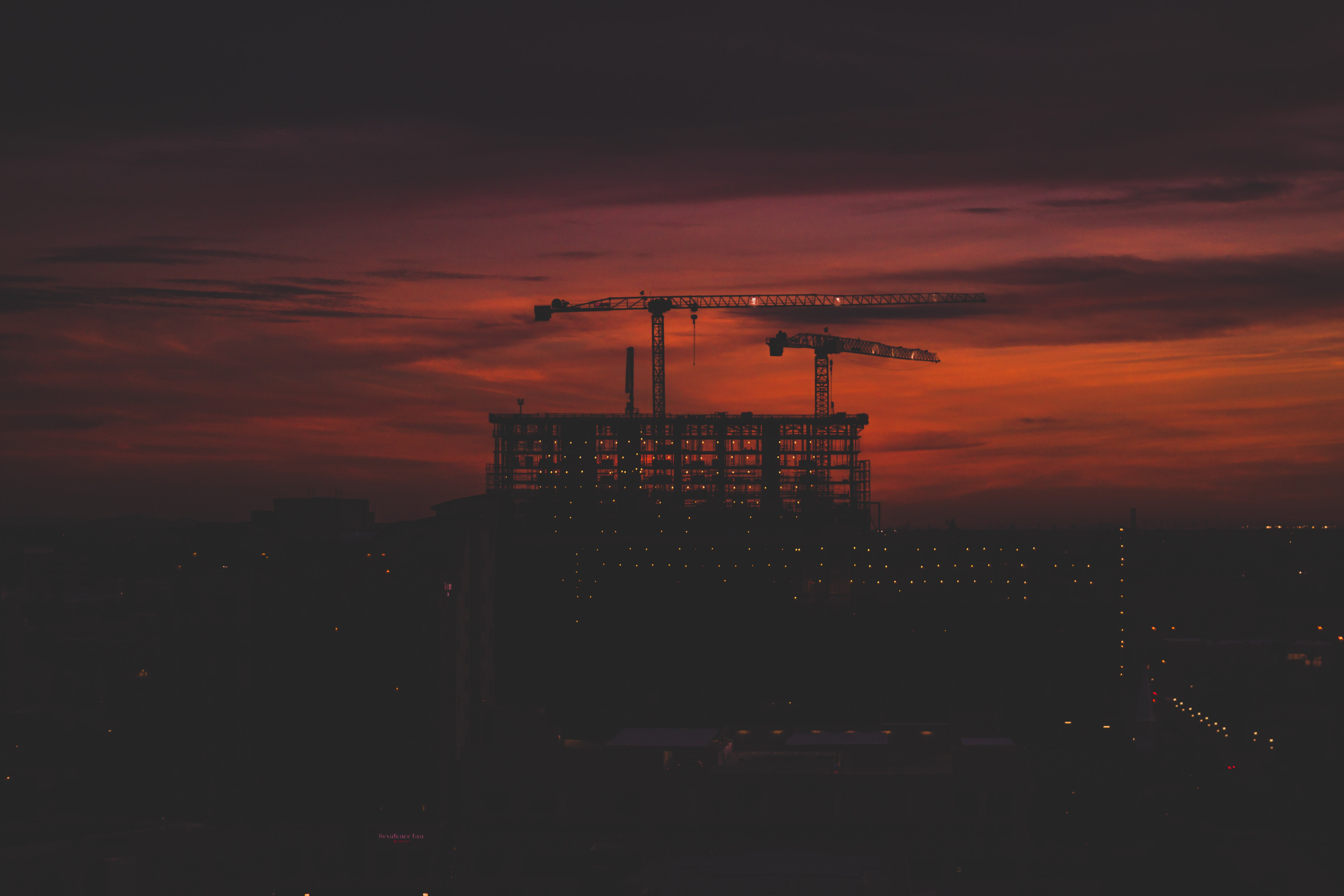 silhouette of crane at top of the building