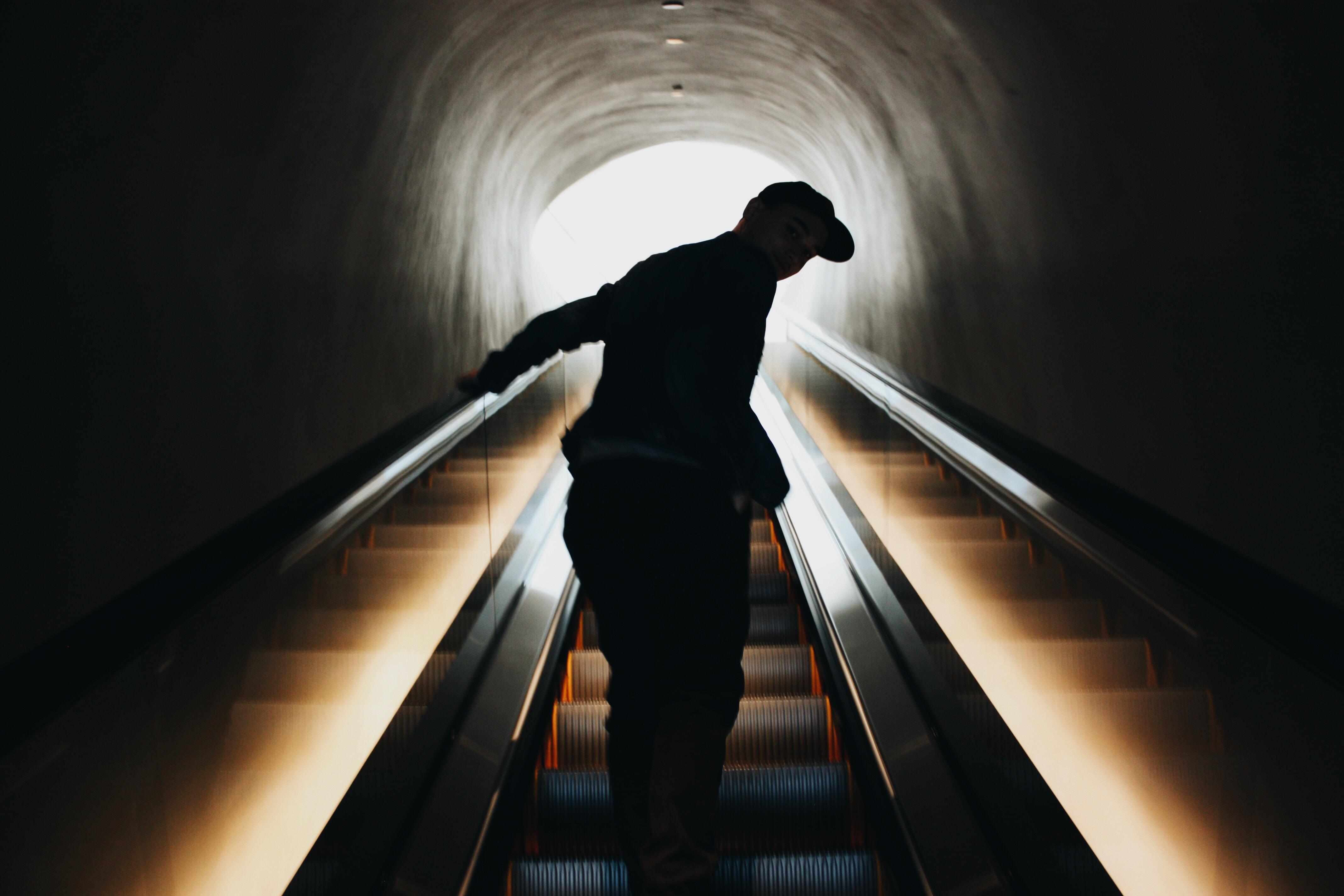 silhouette photo of man standing on escalator