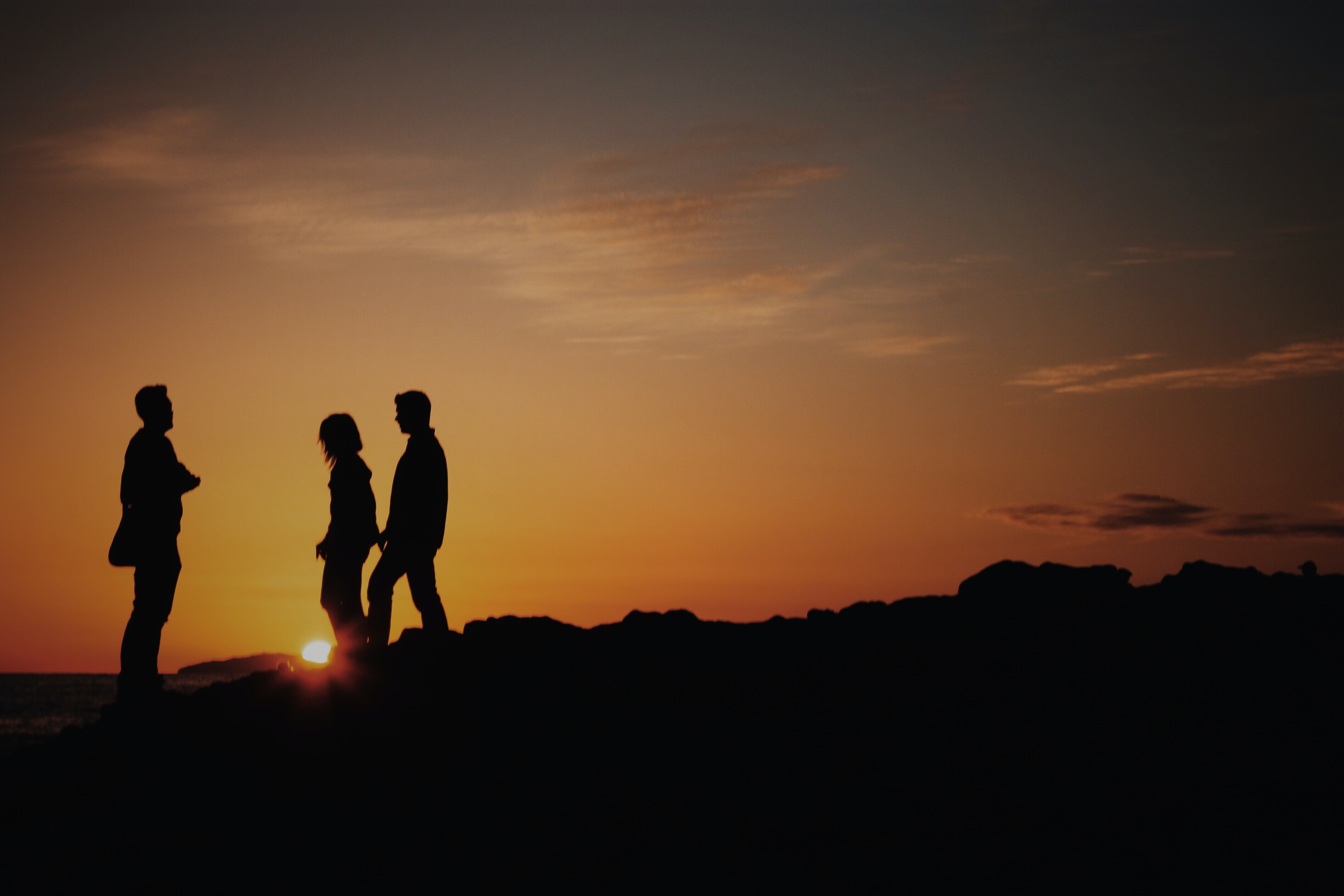 silhouette of two men and one woman on mountain