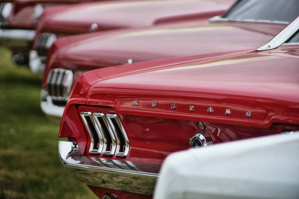 selective focus photography of parked red Ford Mustang cars