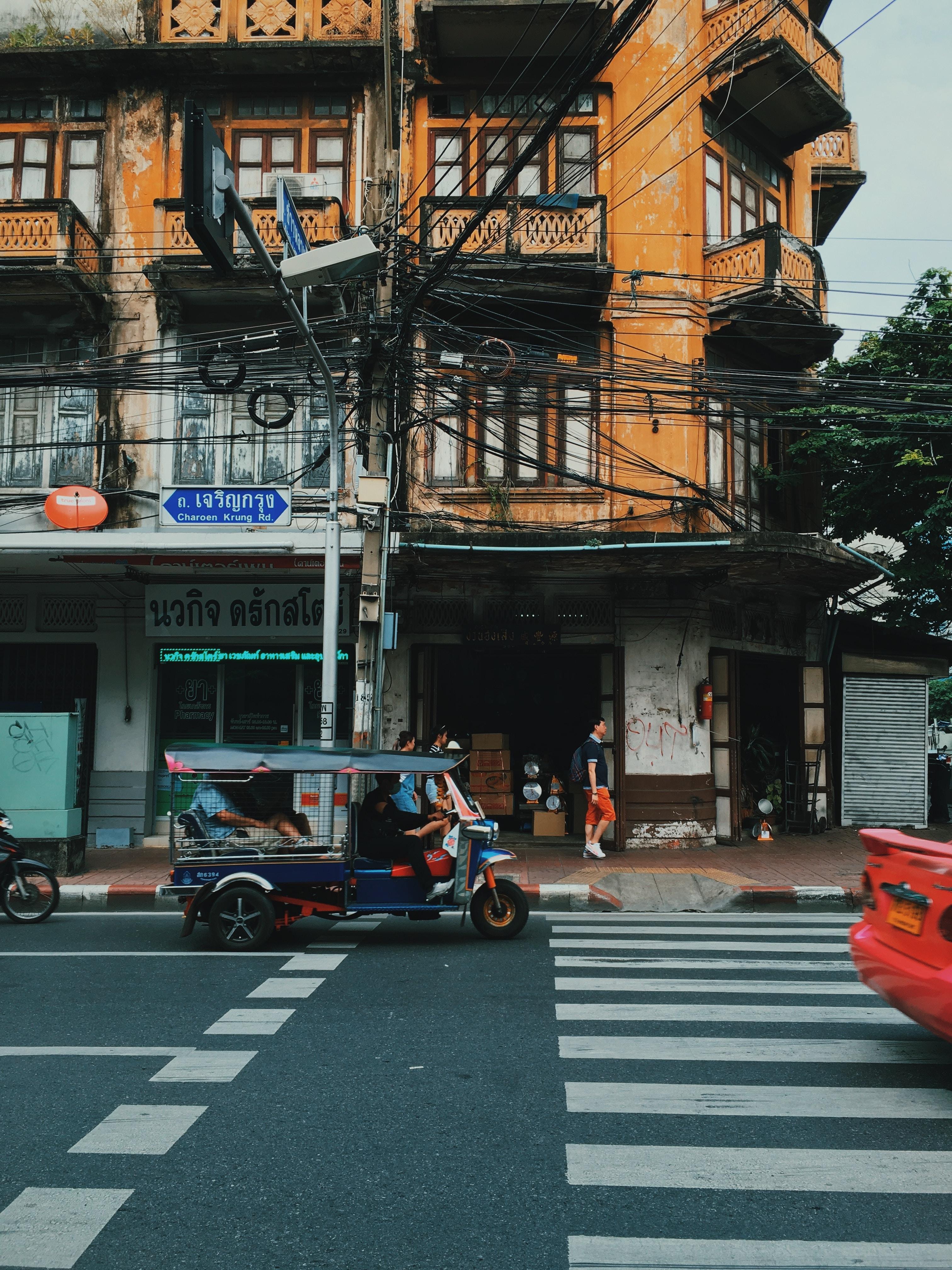 blue auto rickshaw beside building at daytime