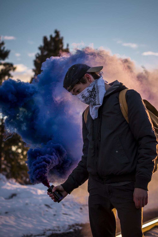 man wearing bandana holding blue smoke can standing