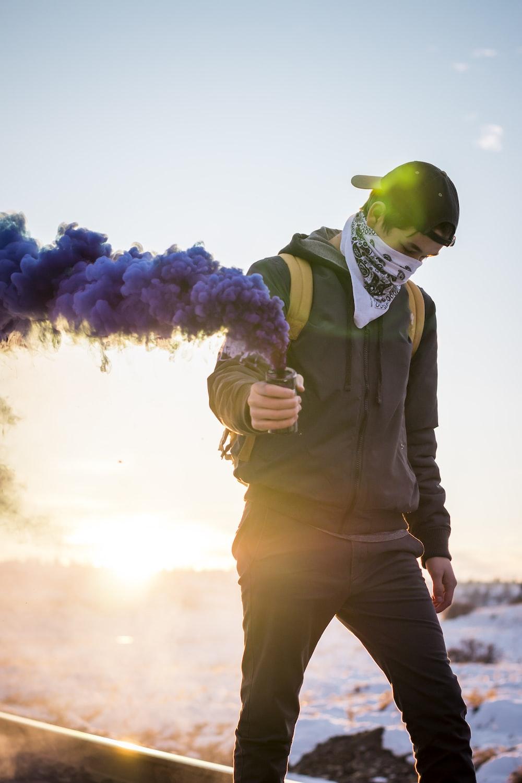 man holding purple flare