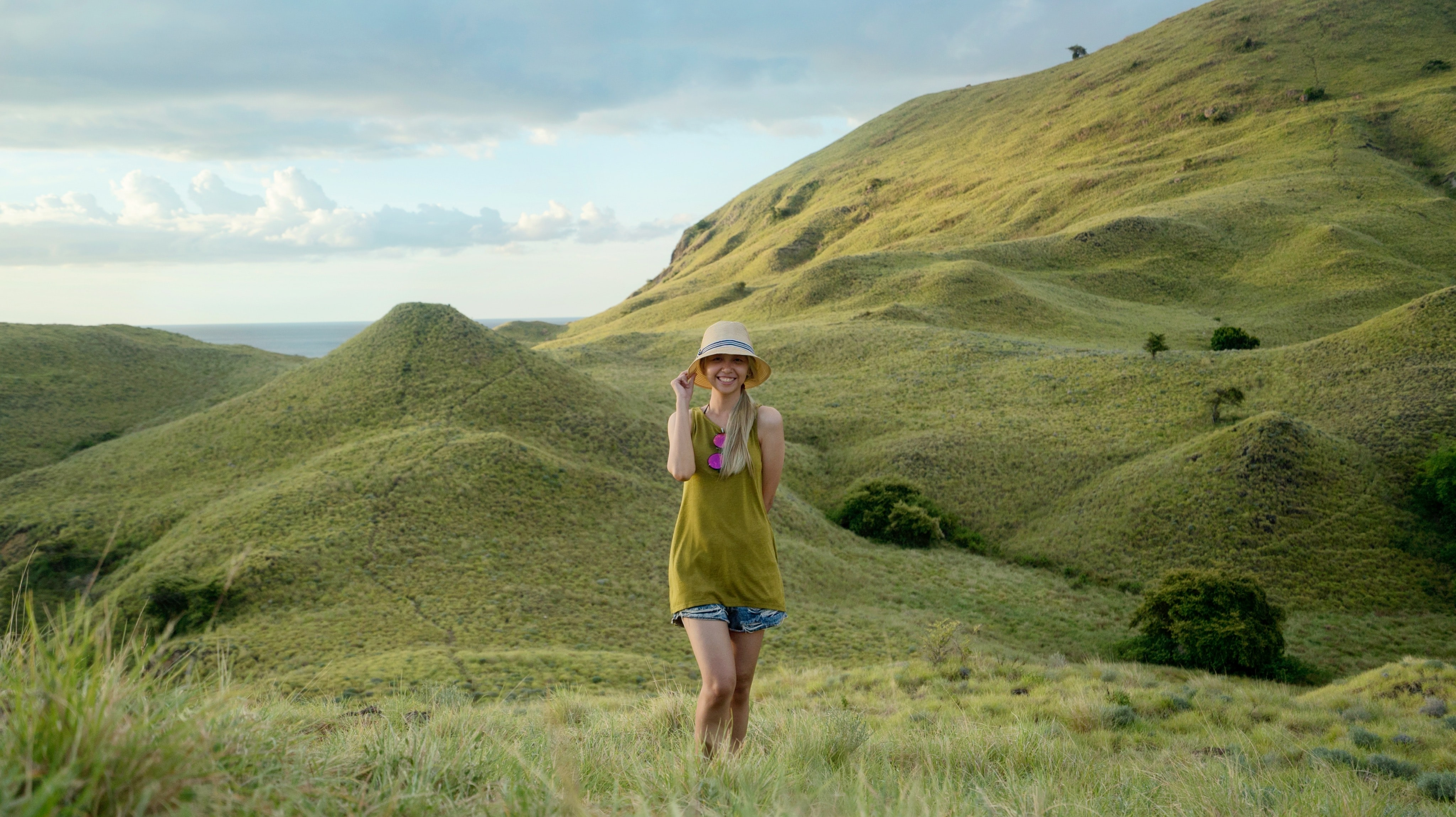 woman in green sleeveless top standing on mountain