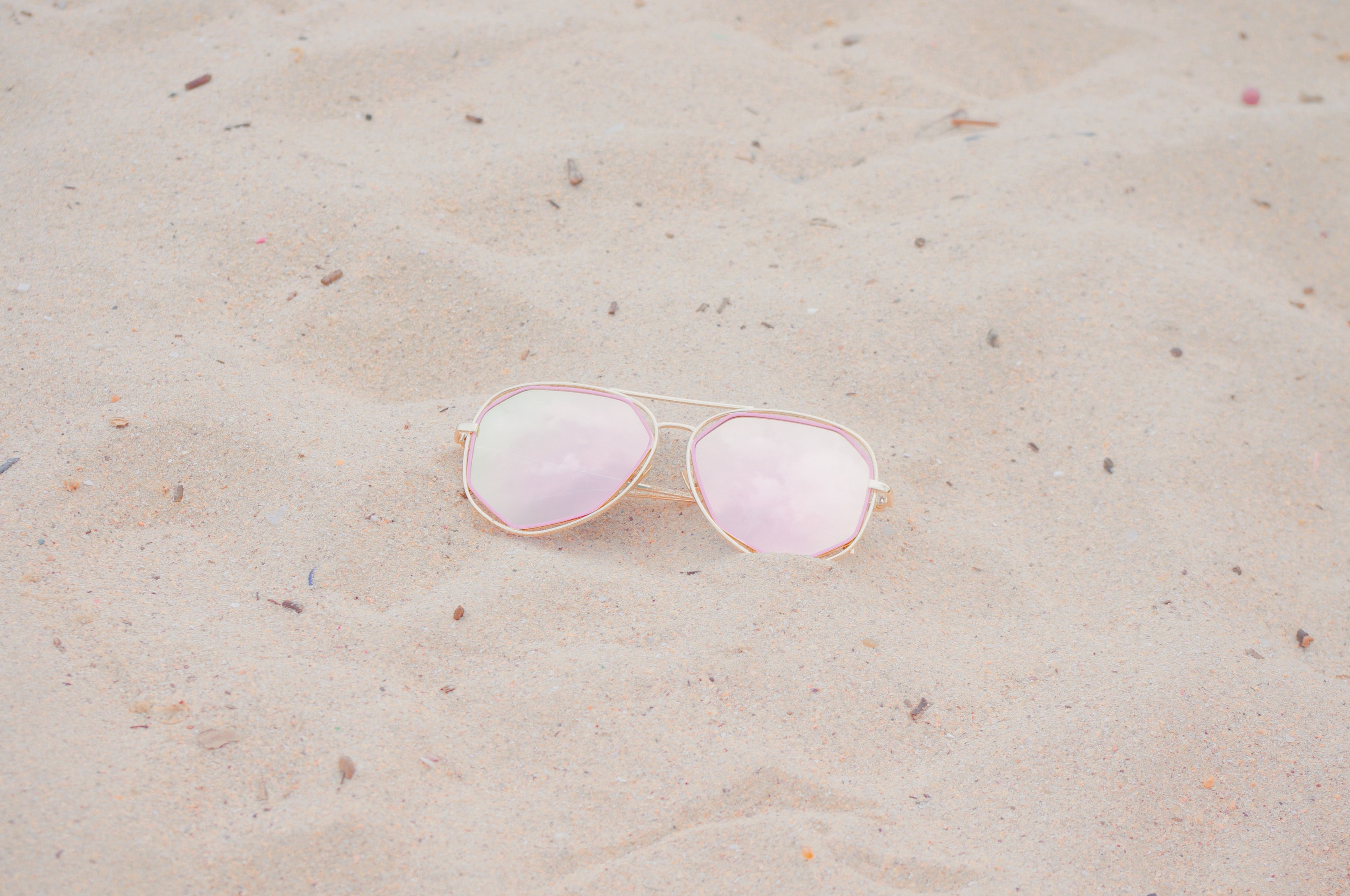 silver framed Aviator-style sunglasses on sand