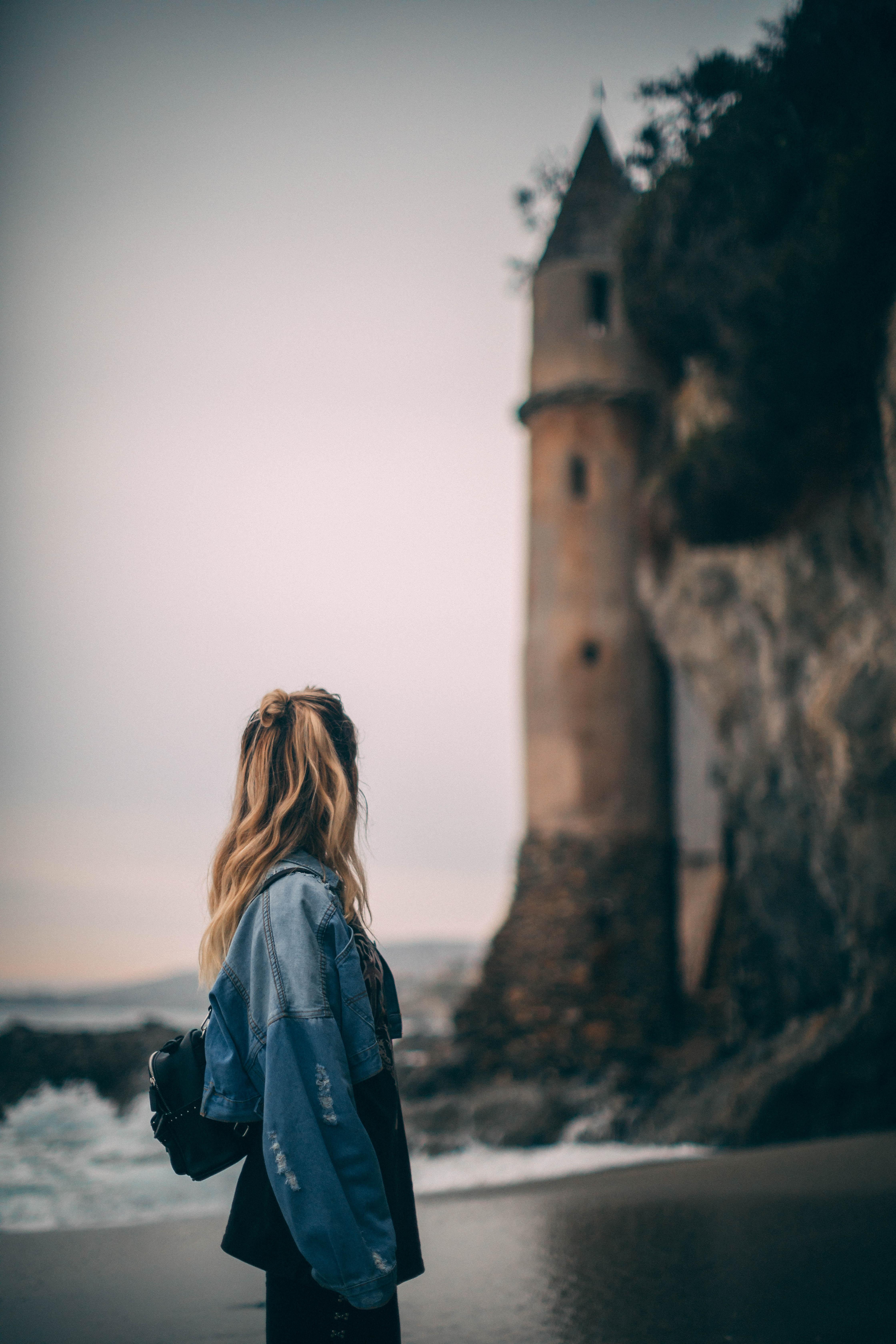selective focus photography of woman on seashore near lighthouse