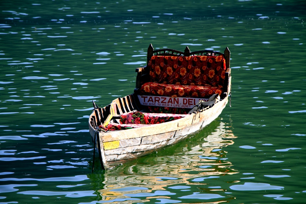 brown wooden boat on body of water