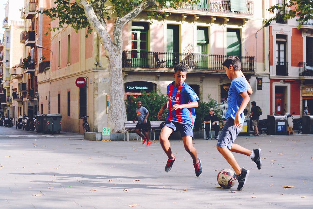 two boy's playing soccer near building during daytime