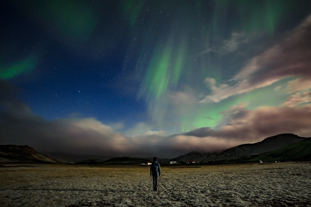 man standing near mountain under Aurora Borealis