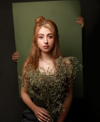 woman holding withered plants