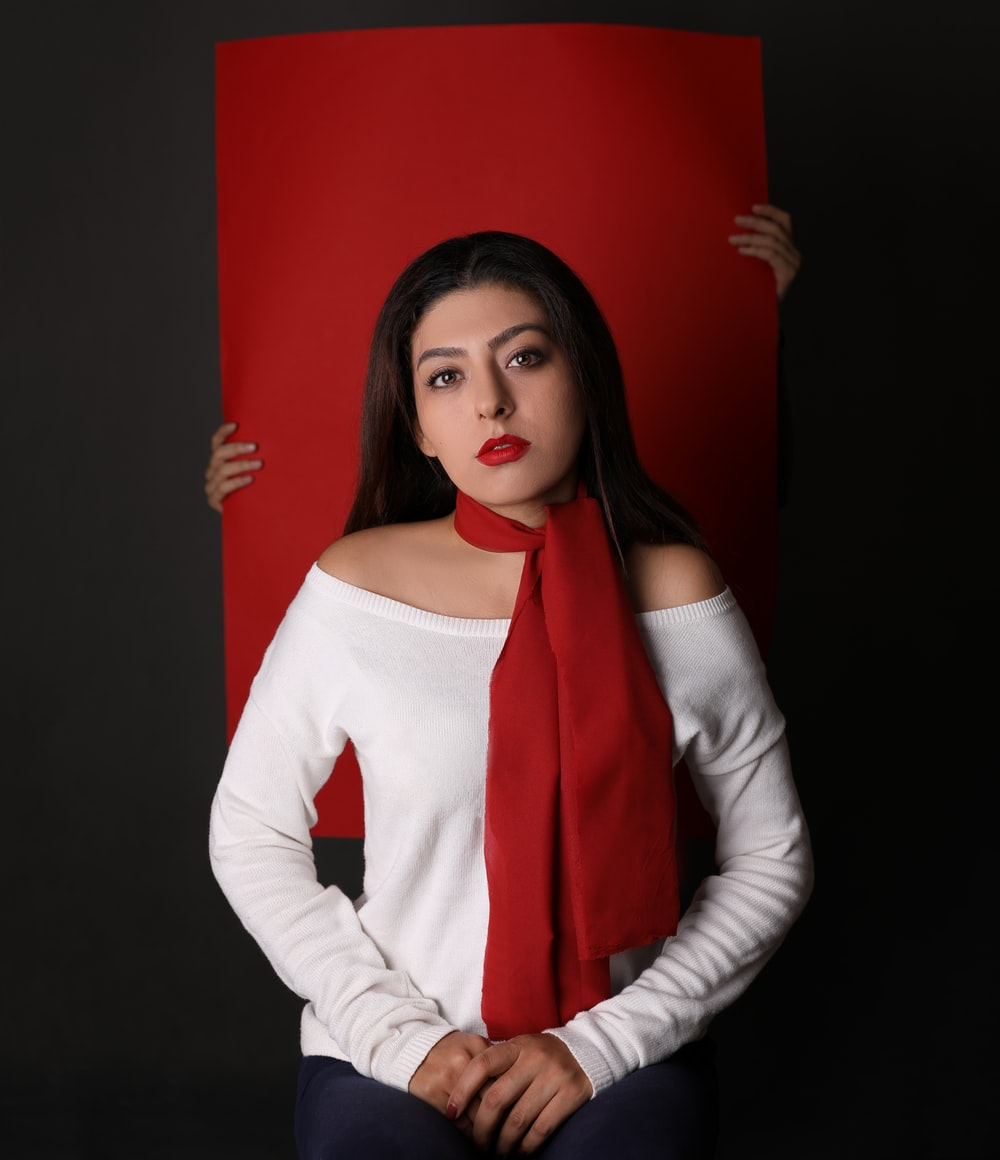 woman in white long-sleeved top and red scarf in front of red paper board