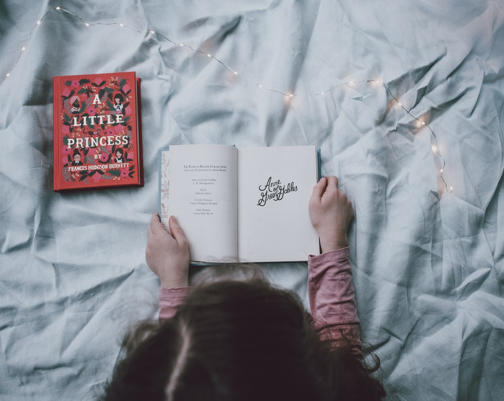 toddler holding book on bed