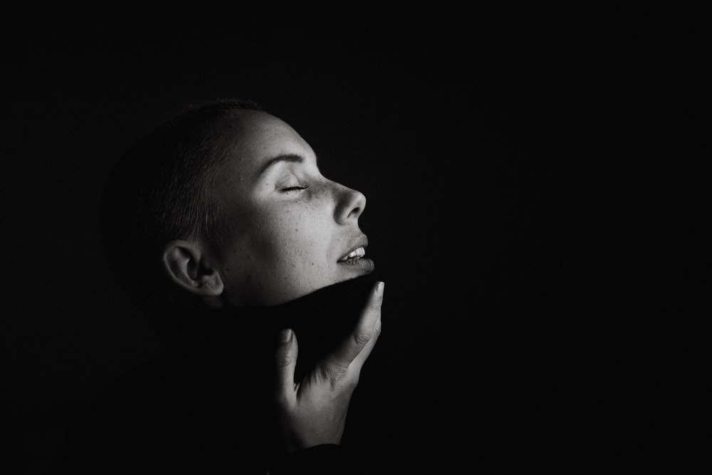 woman with hand on chin gray scale photography