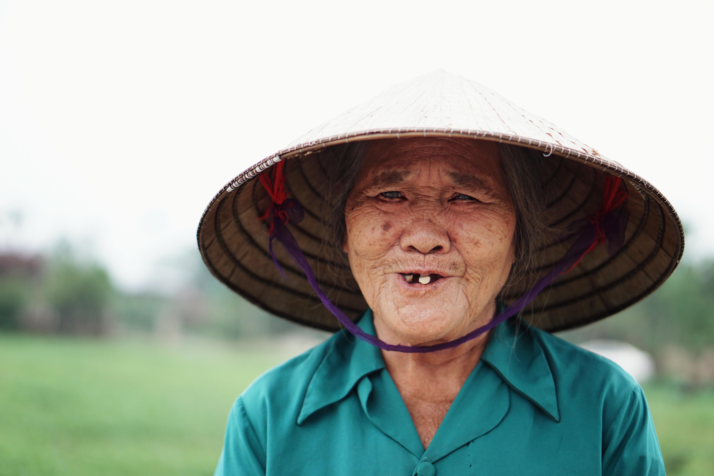 woman wearing woven hat standing near grass