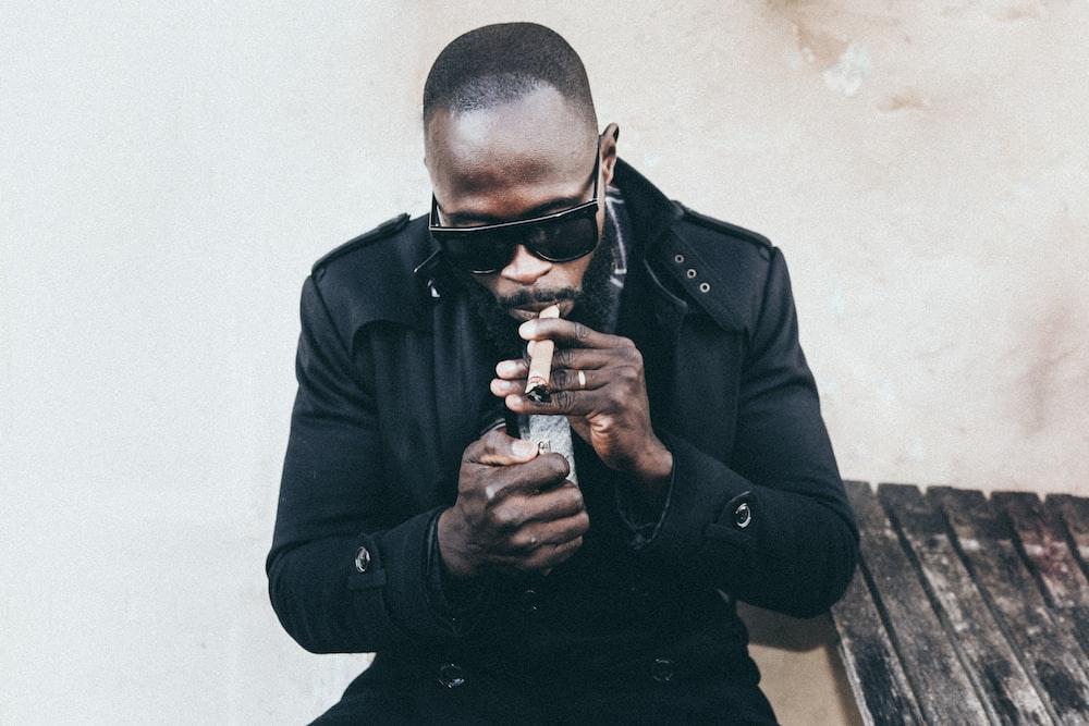 man in black coat holding brown tobacco