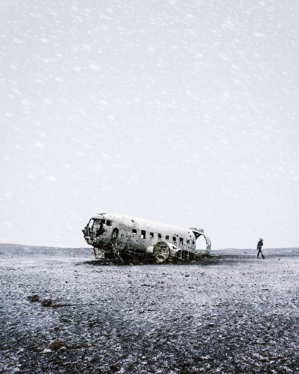 grayscale photo of crushed plane beside person