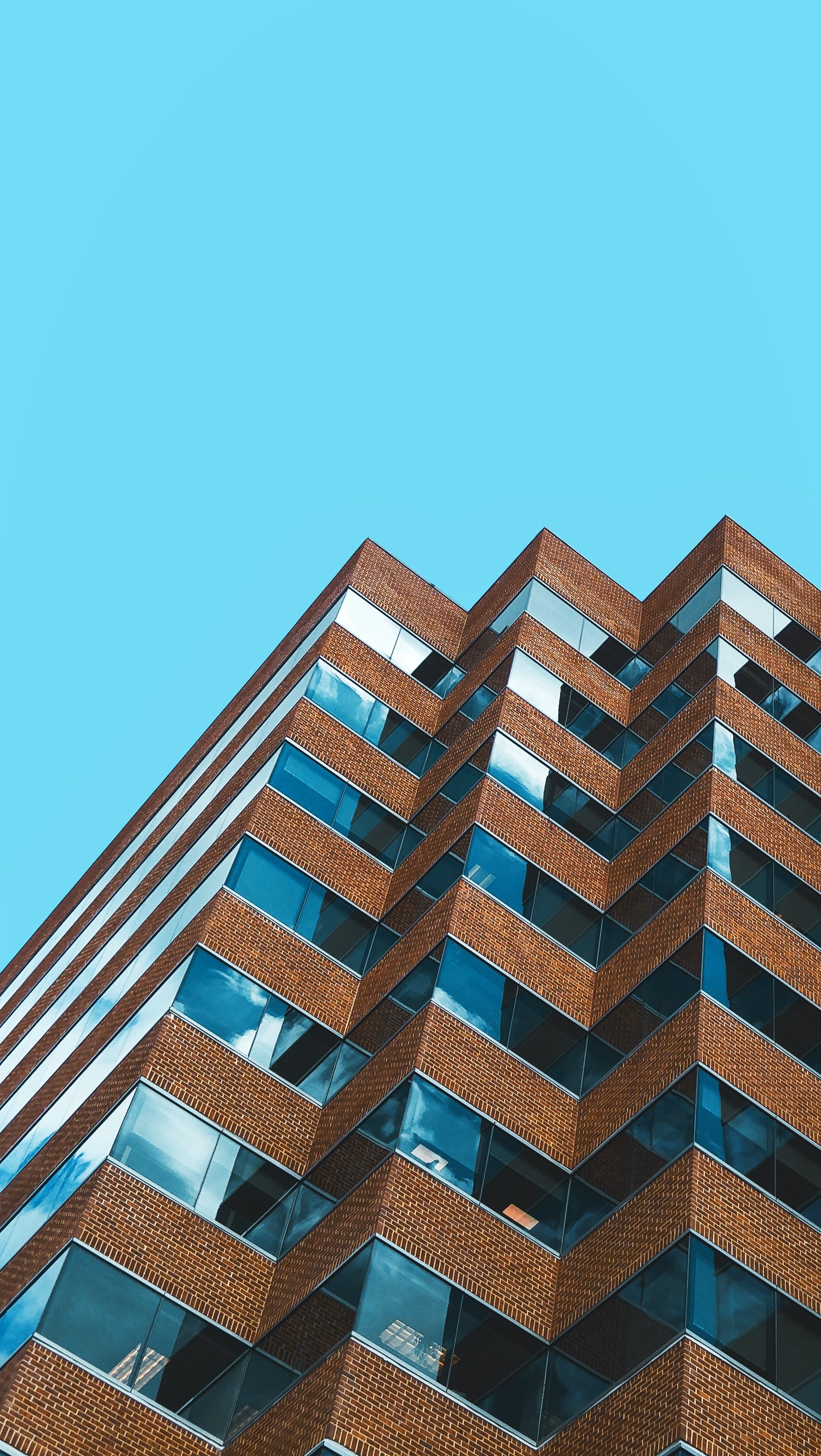 low angle photography of brown and grey high-rise building