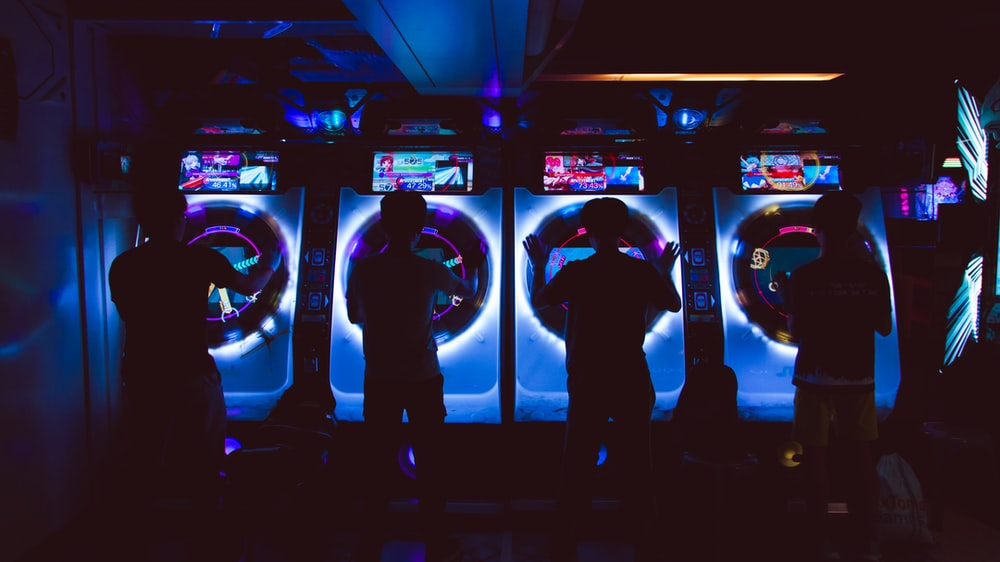 four people playing arcade game