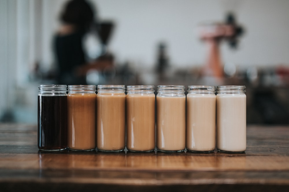seven mason jars of coffee on table