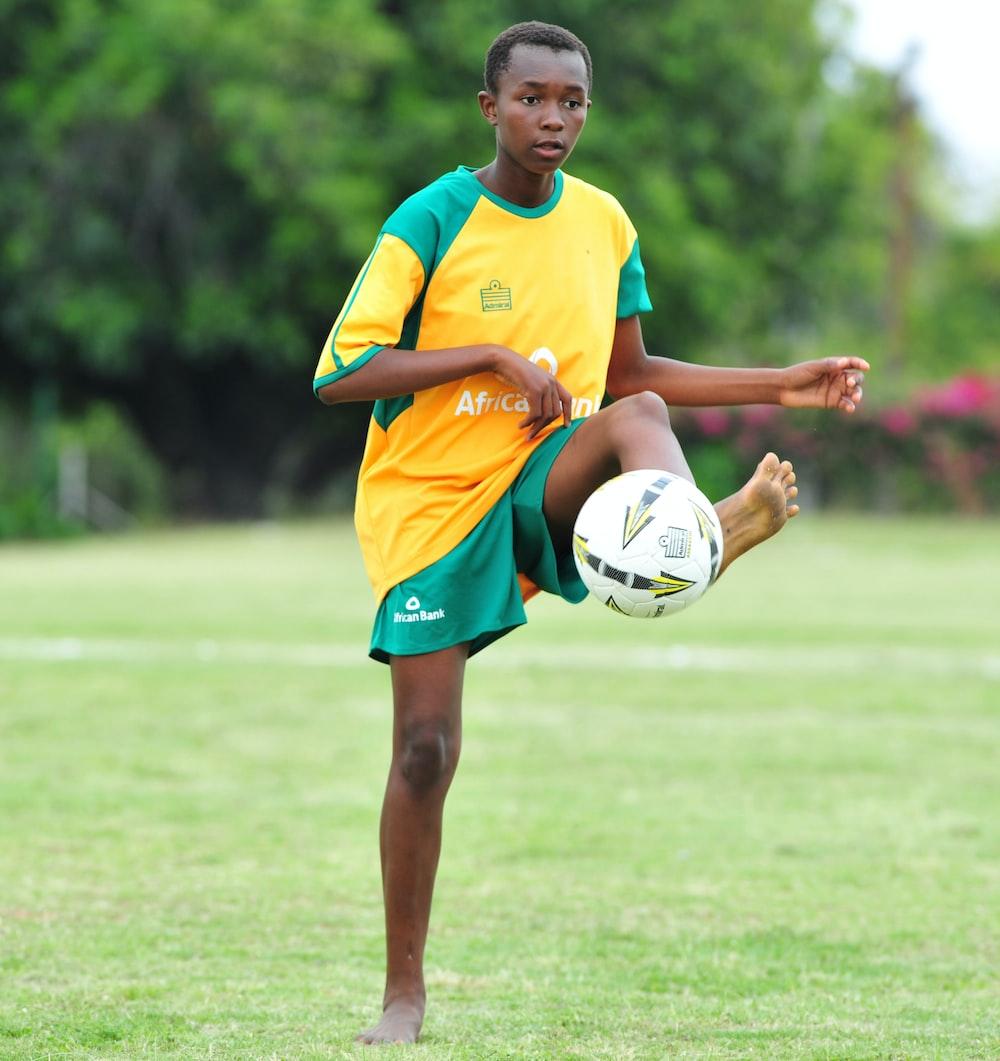 boy playing soccer ball